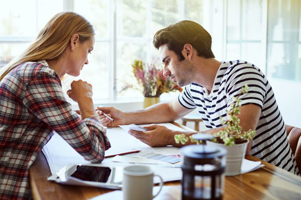 Young couple looking over budget at kitchen table
