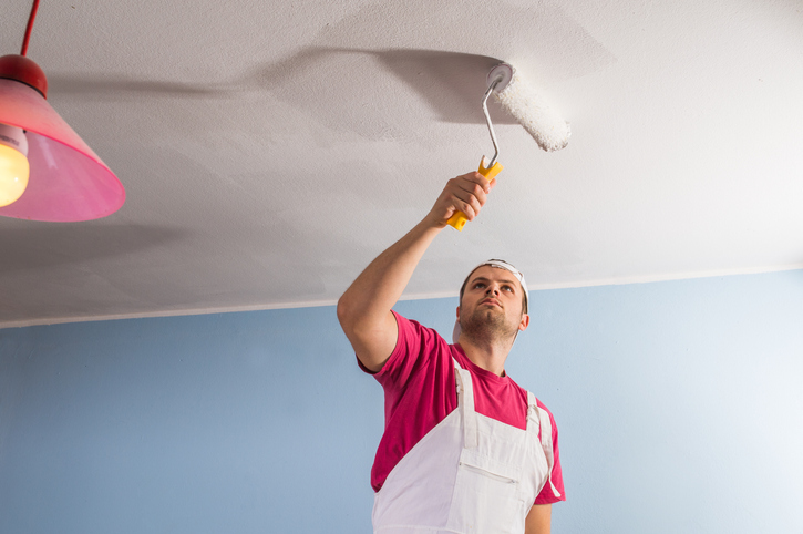 Man painting the ceiling of a living room white. Attempting to hake his low ceiling appear higher.